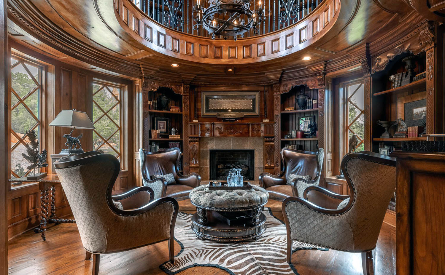 Beautiful round sitting room with all wood walls and ceiling. Wood floors. Fireplace with wood surround.