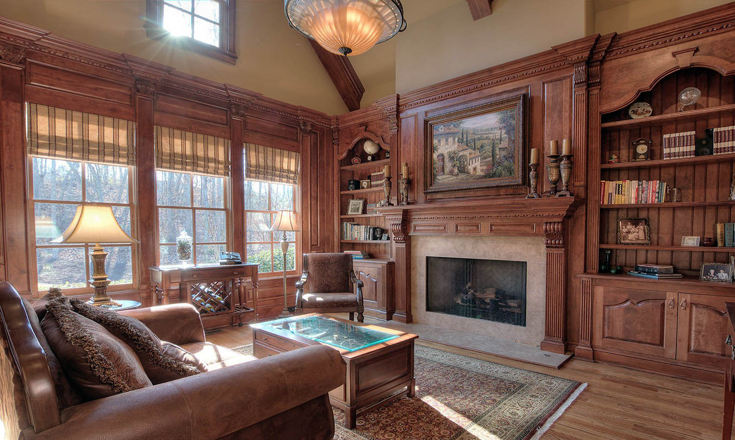 Sitting room with stained wood wall paneling. Vaulted ceiling with wood beams. Fireplace with wood surround. Built in cabinets and shelving.