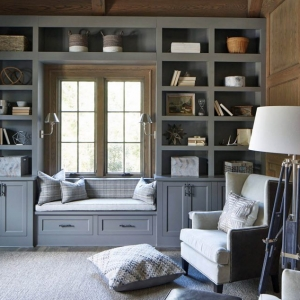 Wood wall paneling with built in shelving, cabinets and window seat. Gray built ins with brown paneling stain. Wood floors with area rug.