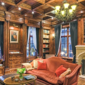 Rustic home office with stained wood walls and matching coffered ceiling with chandelier, large foreplace surround and wood floors.