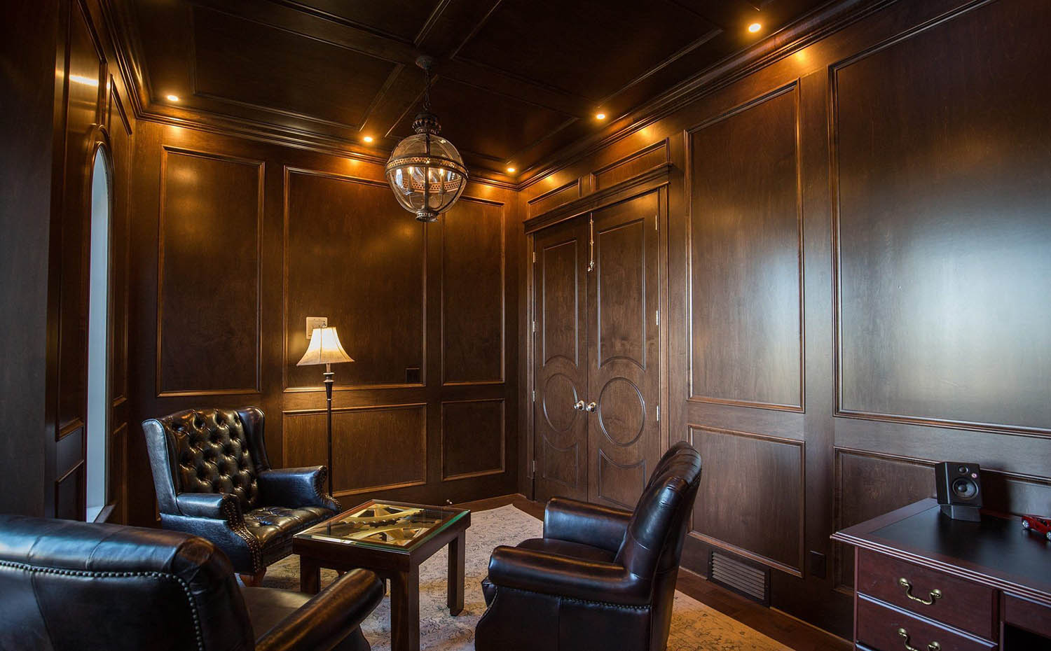 Sitting room with large wood wall panels and matching wood ceiling. Dark brown wood stain. Matching hardwood floors with beige area rug.