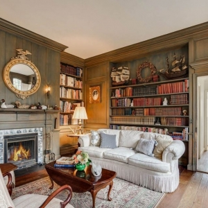 Beautiful sitting room with wood wall paneing. Built in shelving and cabinets. Fireplace with wood surround. Wood floors. Greenish brown stain.