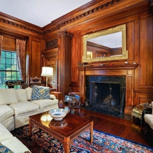 Wooden wall paneling with fireplace. Wood surround. Wood floors. Thick crown molding and custom trim. Plush white sofas.