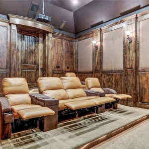 Theatre room with wood walls and carpeting. Leather recliners.