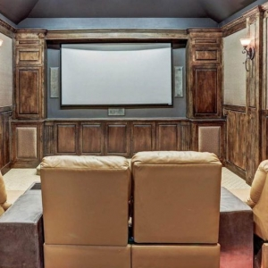 Wooden walls in a home theatre room with leather recliners.