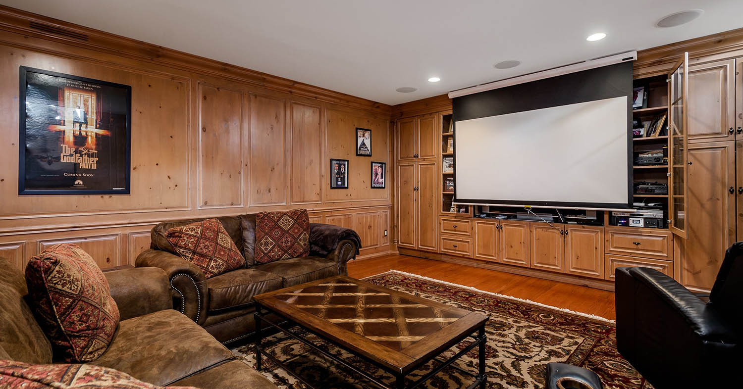 Living room with all wood wall paneling and built ins. Hardwood floors. Brown leather sofas.