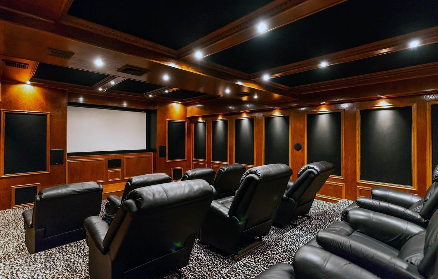 Home theatre room with all wood walls and wood ceiling. Black leather recliners.