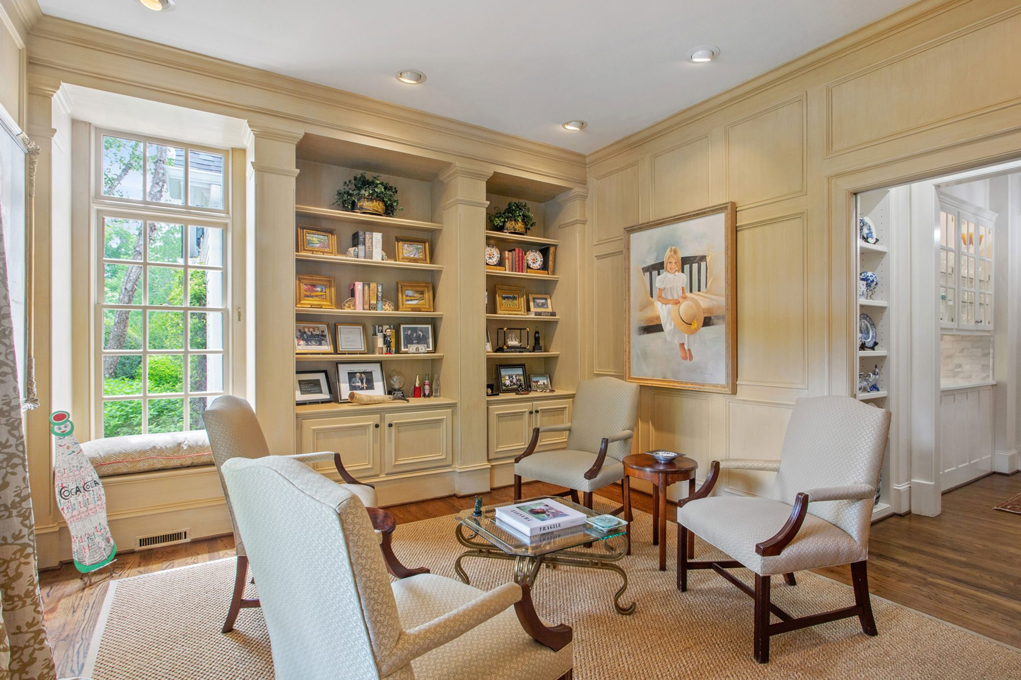 Whitewashed light colored antique wood walls in a beautiful sitting room. Built in shelving and cabinetry, wood floors and a beige area rug. Dark wood chairs with light colored cream cushions. Window seat.