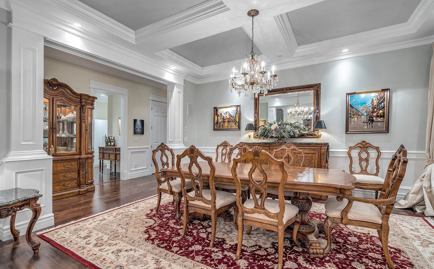 Dining room coffered ceiling with gray walls and cofferes, white beams with crown molding, center chandelier.