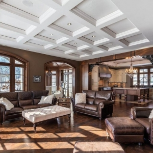 Beautiful living room with all white coffered ceiling recessed into the ceiling with soffits. Recessed LED lighting. Brown walls with brown stained trim.