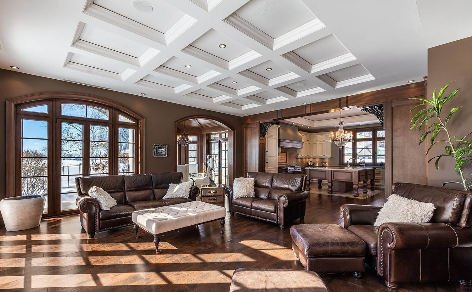 living room with brown walls and wood trim with a recessed white coffered ceiling
