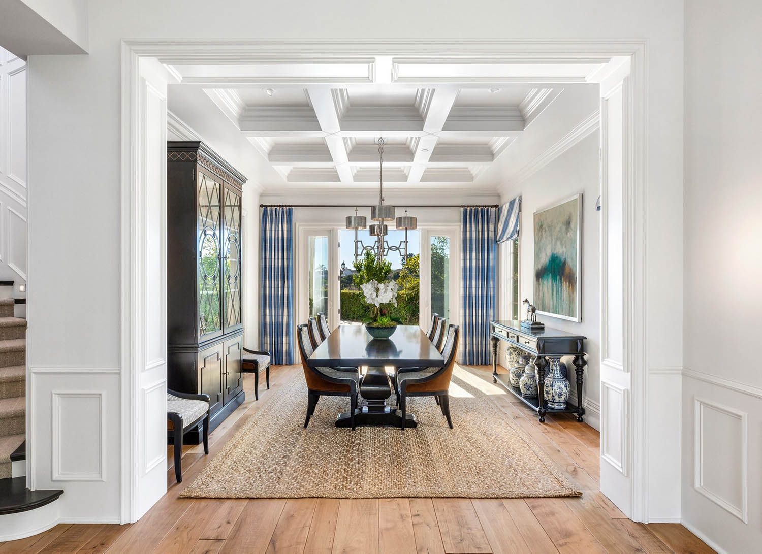 All white dining room design with coffered ceiling and soffits. Natural wide plank hardwood floors.