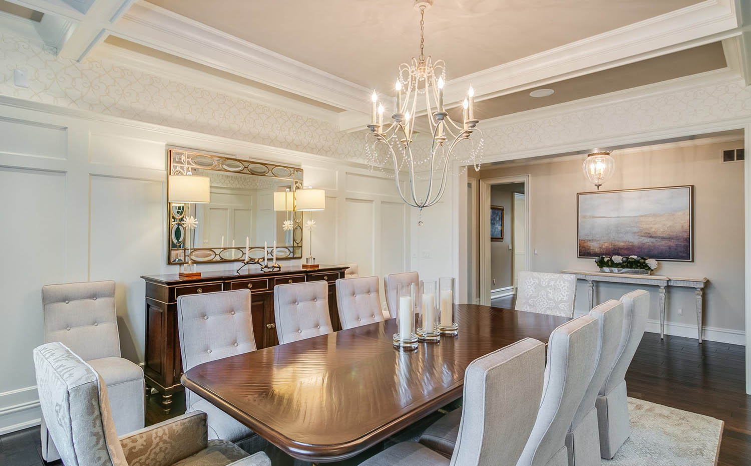 Tan dining room design with white wall paneling and white coffered ceiling beams with tan coffers. Chandelier.