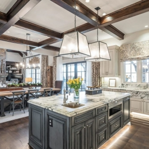 beautiful kitchen gray center island with marble countertop, dark wood stained coffered ceiling. Open floor plan.