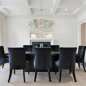All white dining room with white coffered ceiling with black table and plush chairs. Dark hardwood floors with tan area rug.