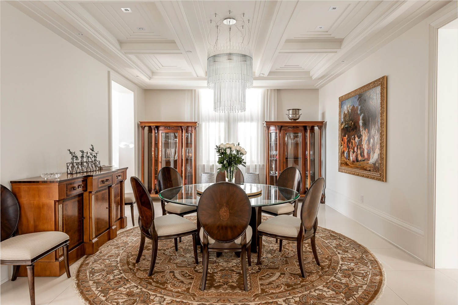 Simple dining room with a beautiful coffered ceiling. White beams and coffers with a crystal chandelier. Round glass table with wood chairs.