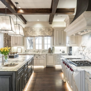 Luxury kitchen with marble slab backsplash, wolf stove, marble countertops, dark wood coffered ceiling.