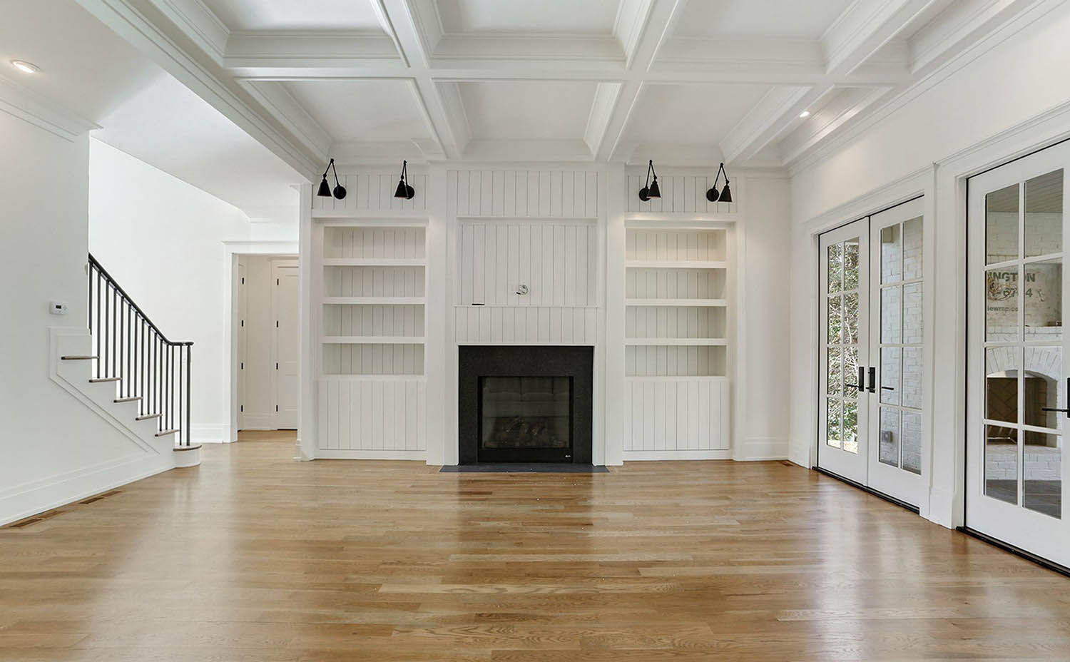 white living room coffered ceiling in an all white room with built ins light hardwood floor
