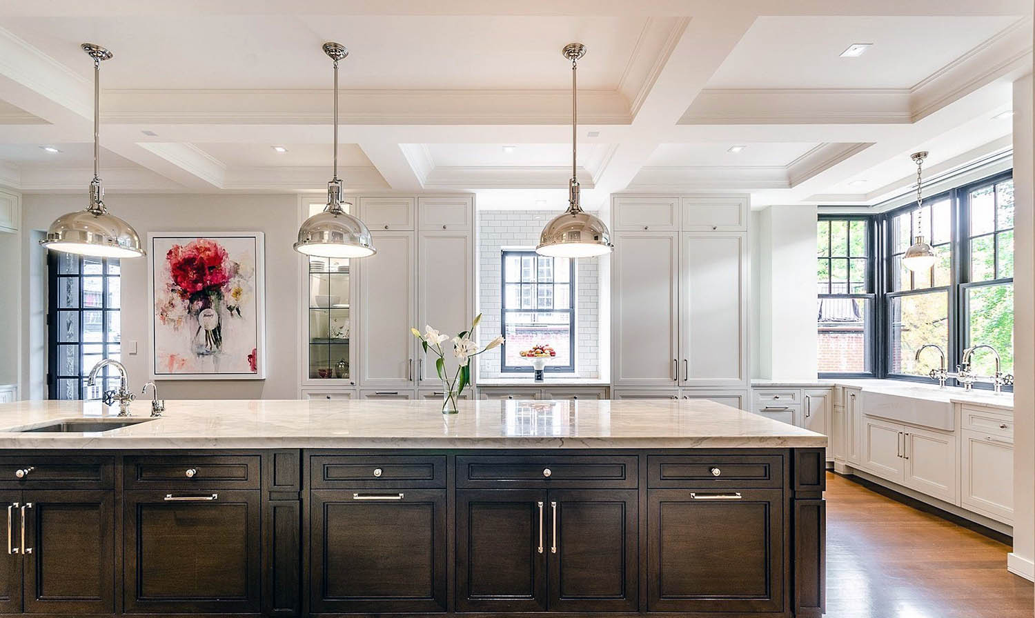 high end kitchen with dark woodisland and white coffered ceiling