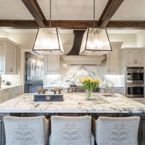 Custom high end kitchen with marble countertops and solid slab backsplash, Dark wood coffered ceiling.