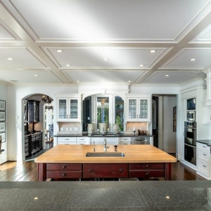 Low profile coffered ceiling in a custom kitchen. White beams and coffers with recessed lighting.