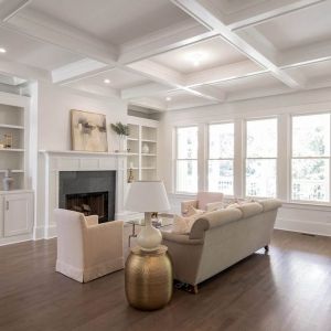 Living room coffered ceiling. White walls and ceiling. White trim and built ins with gray tile fireplace surround.