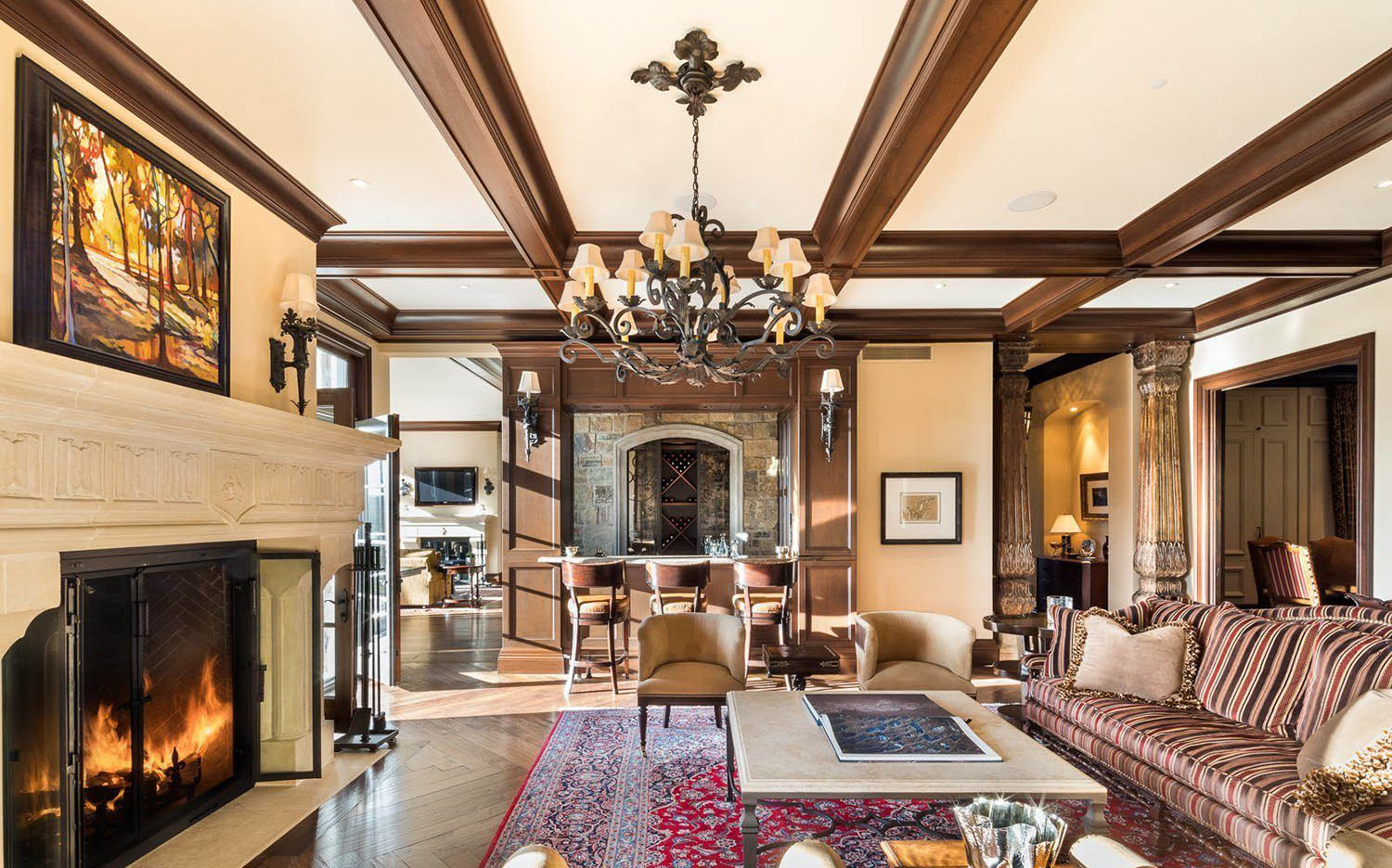 Beautiful living room with brown neutral color palette. Real wood stained coffered ceiling with iron chandelier.