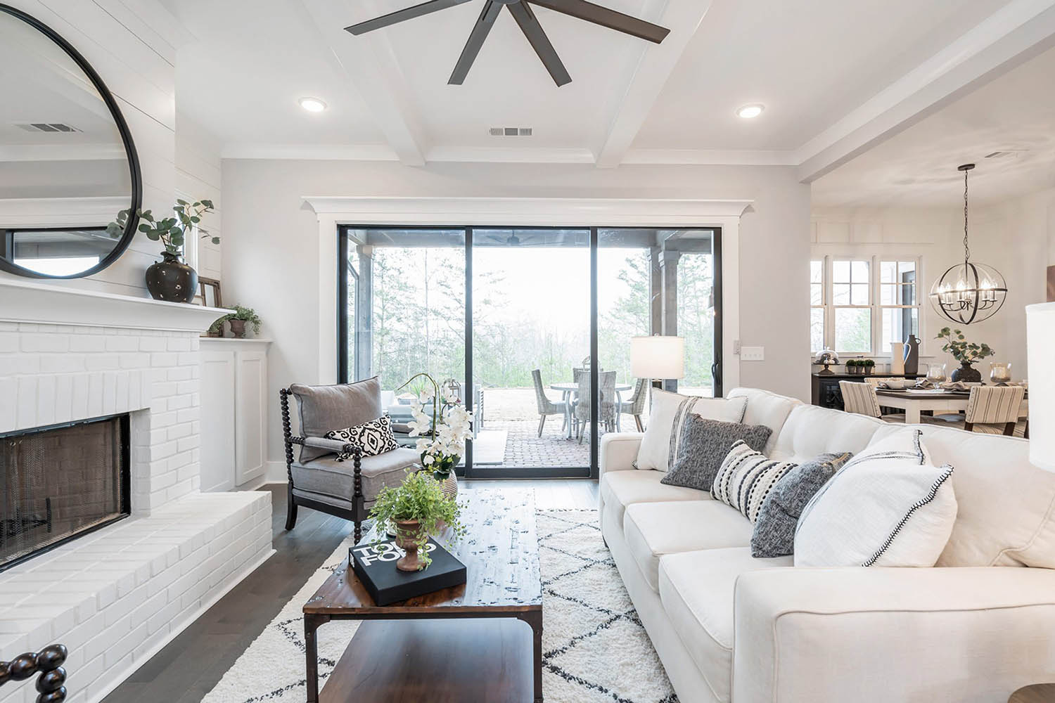 transitional living room with painted white brick and shiplapfireplace and simple coffered ceiling