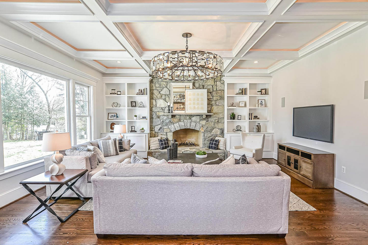 living room coffered ceiling with grid design and center chandelier real stone veneer fireplace