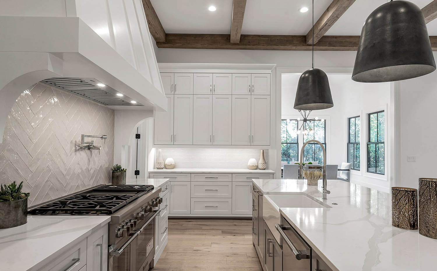 exposed wood beam coffered ceiling in a modern white kitchen with marble countertops