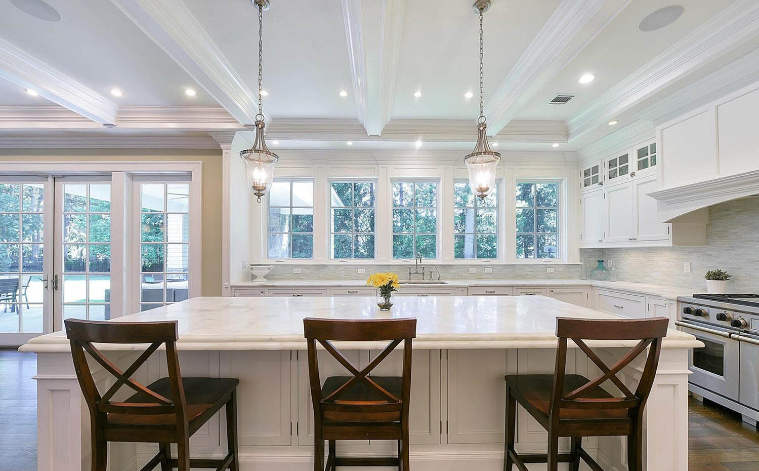 all white coffered ceiling in a luxury white kitchen with dark brown island chairs