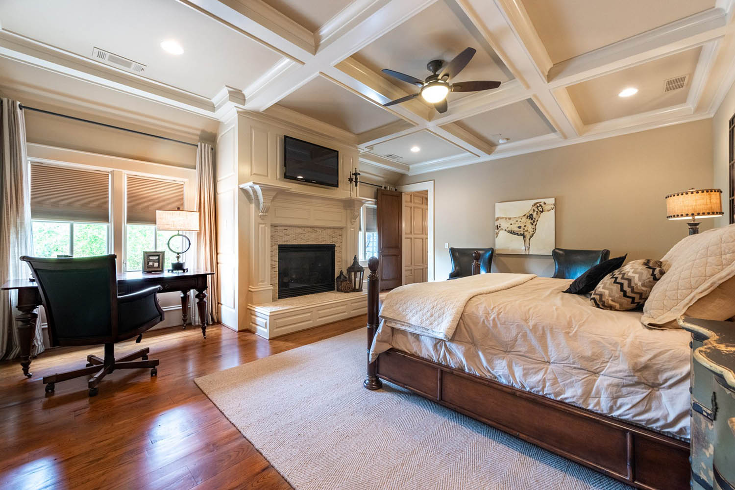 Master bedroom coffered ceiling with white beams and tan coffers. Gas fireplace with tile and wood surround.