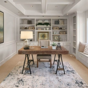 Home office coffered ceiling with soffits. All white ceiling and walls with white trim and wall paneling. Wood desk with metal black legs. Built ins and window seat.