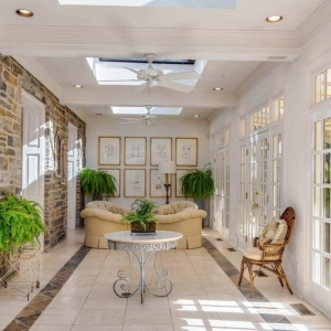 Sunroom coffered ceiling. White beams and coffers. Tile floors with inlay. White walls and ceiling. Stone veneer walls.