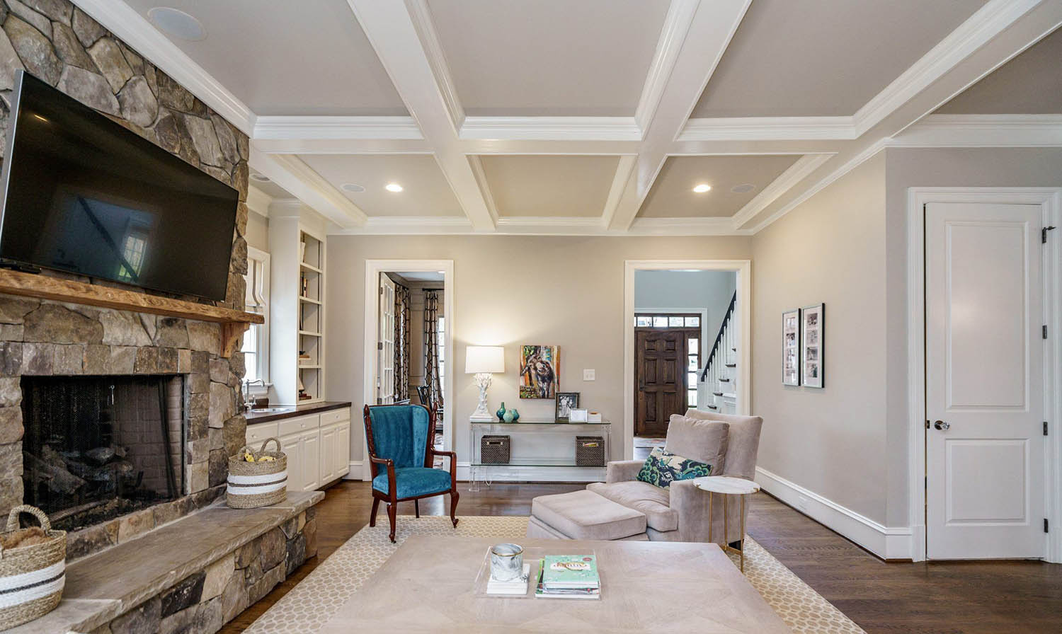 Living room coffered ceiling. 2 Tone design. White beams with gray coffers and recessed lighting. Real stone veneer fireplace surround.