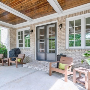 Outdoor covered patio with tan brick walls. Outdoor coffered ceiling, white beams with beadboard.