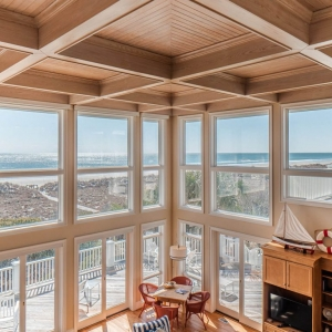 Ocean front beach house with cathedral ceilings, all tan wood with bead board coffers.