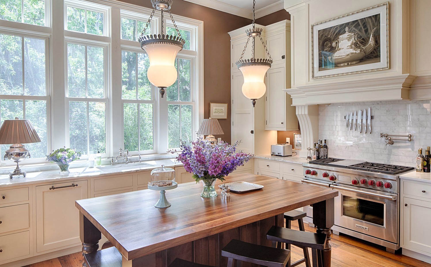 Beautiful cream colored kitchen with brown walls and marble backsplash. Wood floors with matching wood island and stools. Dark bronze hardware. Marble countertops.