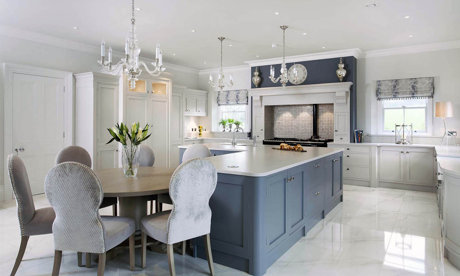 Light gray cream kitchen cabinets with a navy blue island. Light gray countertops.