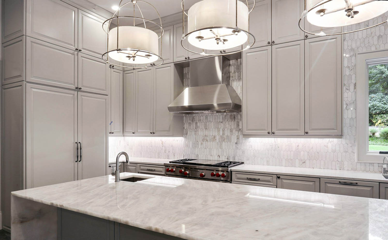 Beautiful kitchen design featuring warm gray cream cabinets and marble.