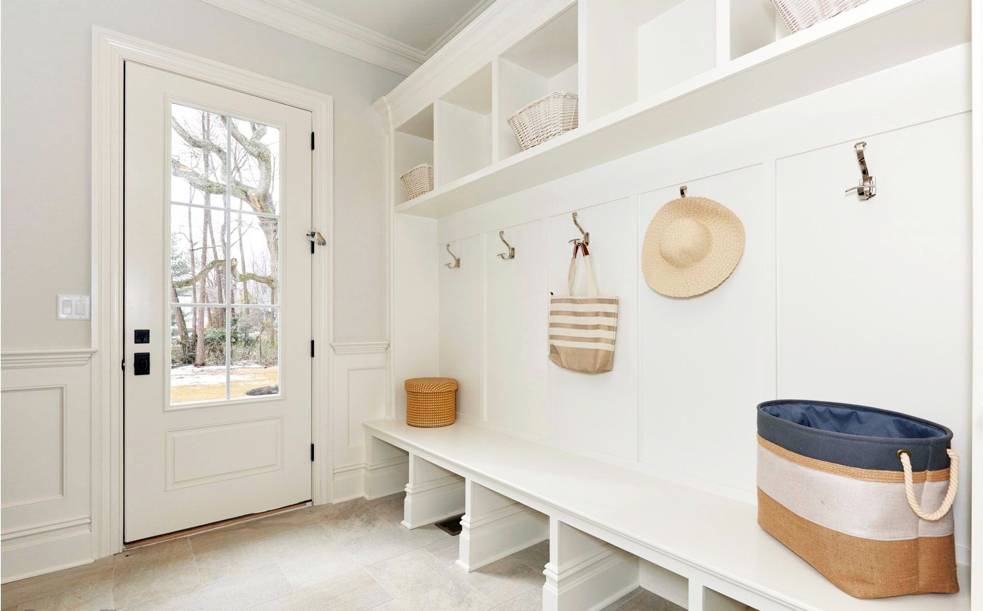 large white mudroom with built in bench storage and wainscoting