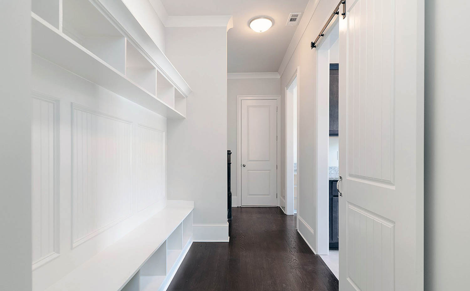 all white built in mudroom storage with high and low cubbies, bench seating and top shelf