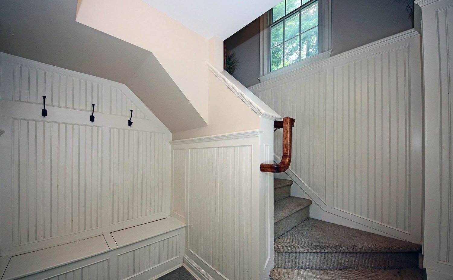 Small mudroom at the base of the stairs in a bi level home