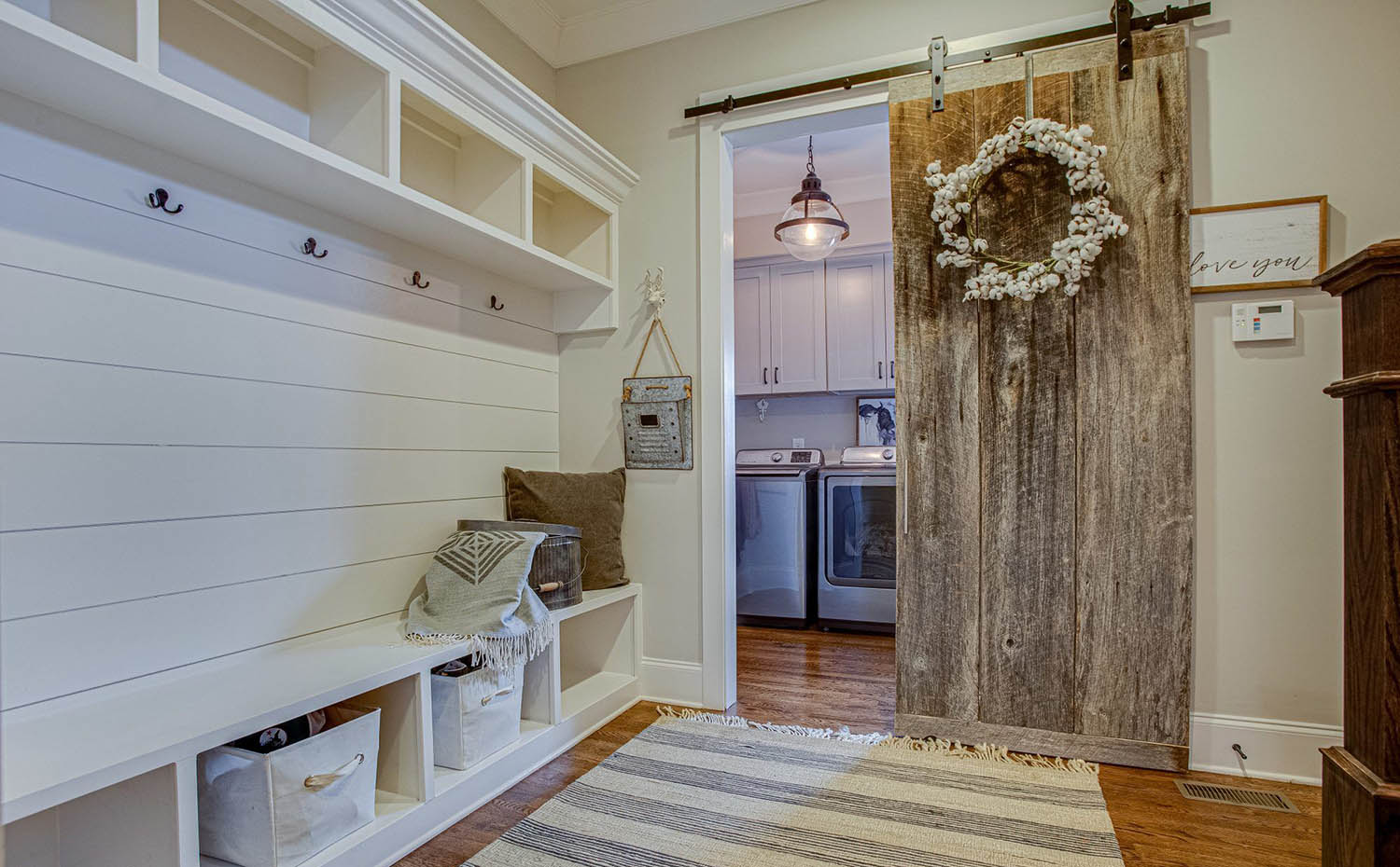 Large mudroom storage with barn door and adjacent laundry room
