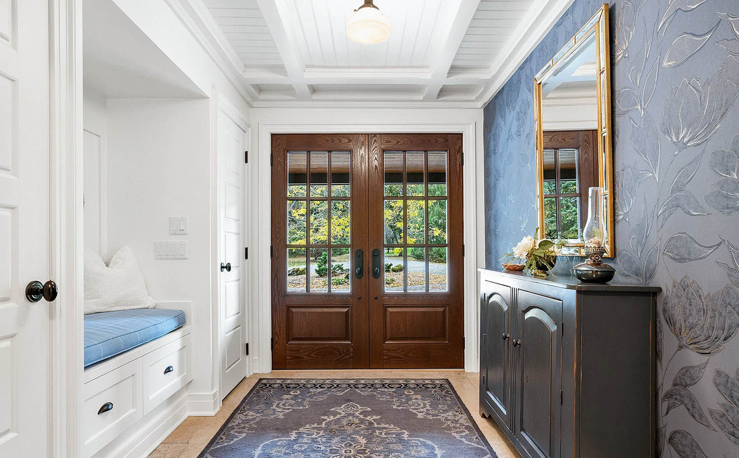 beautiful mudroom with wood flooring and a throw rug with built in bench seating