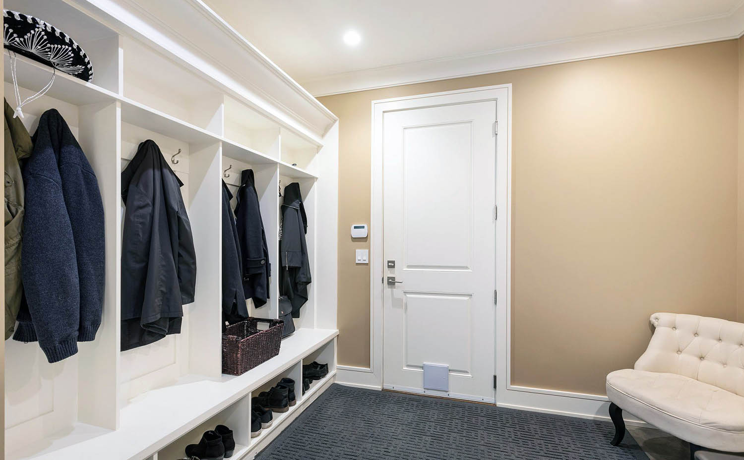 mudroom lockers with shoe storage, tile floors with an area rug