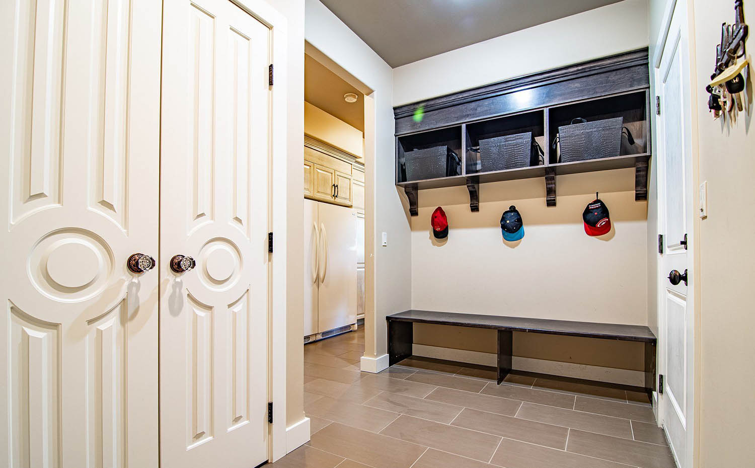 large mudroom with bench, hooks, shelves, cubbies and laundry closet