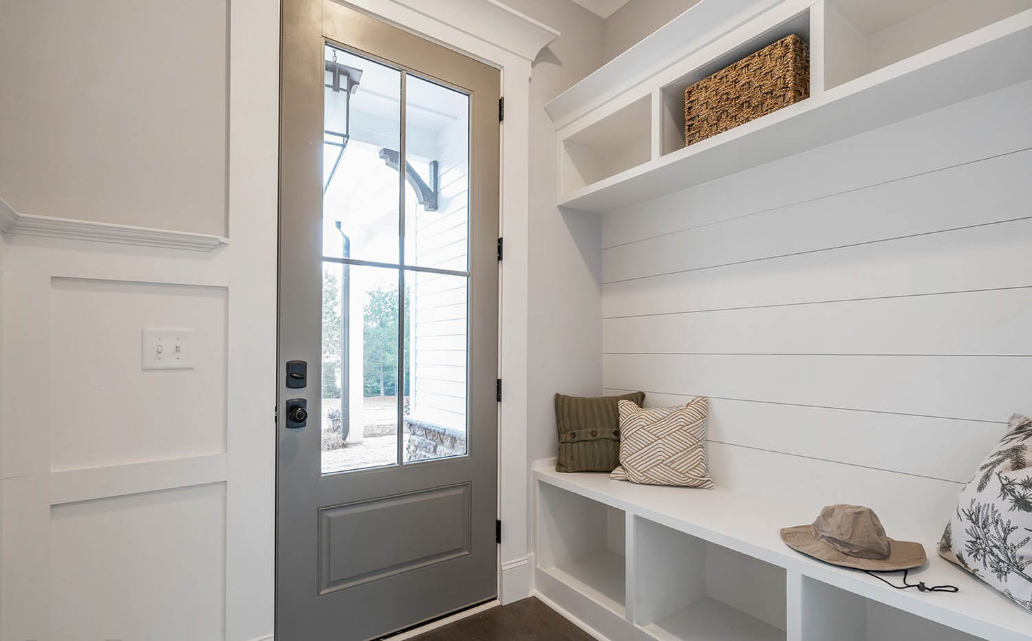 simple, small, white mudroom storage unit with cubbies and bench seat