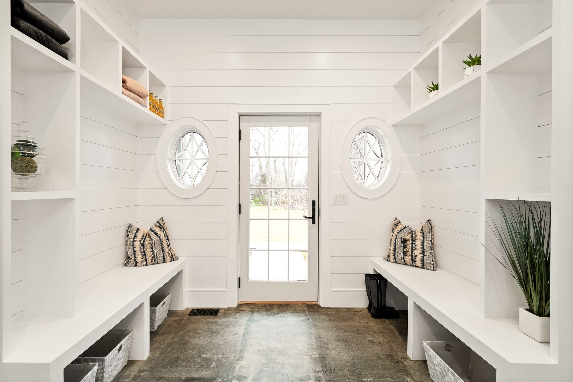 large mud room design with shiplap walls and built in storage