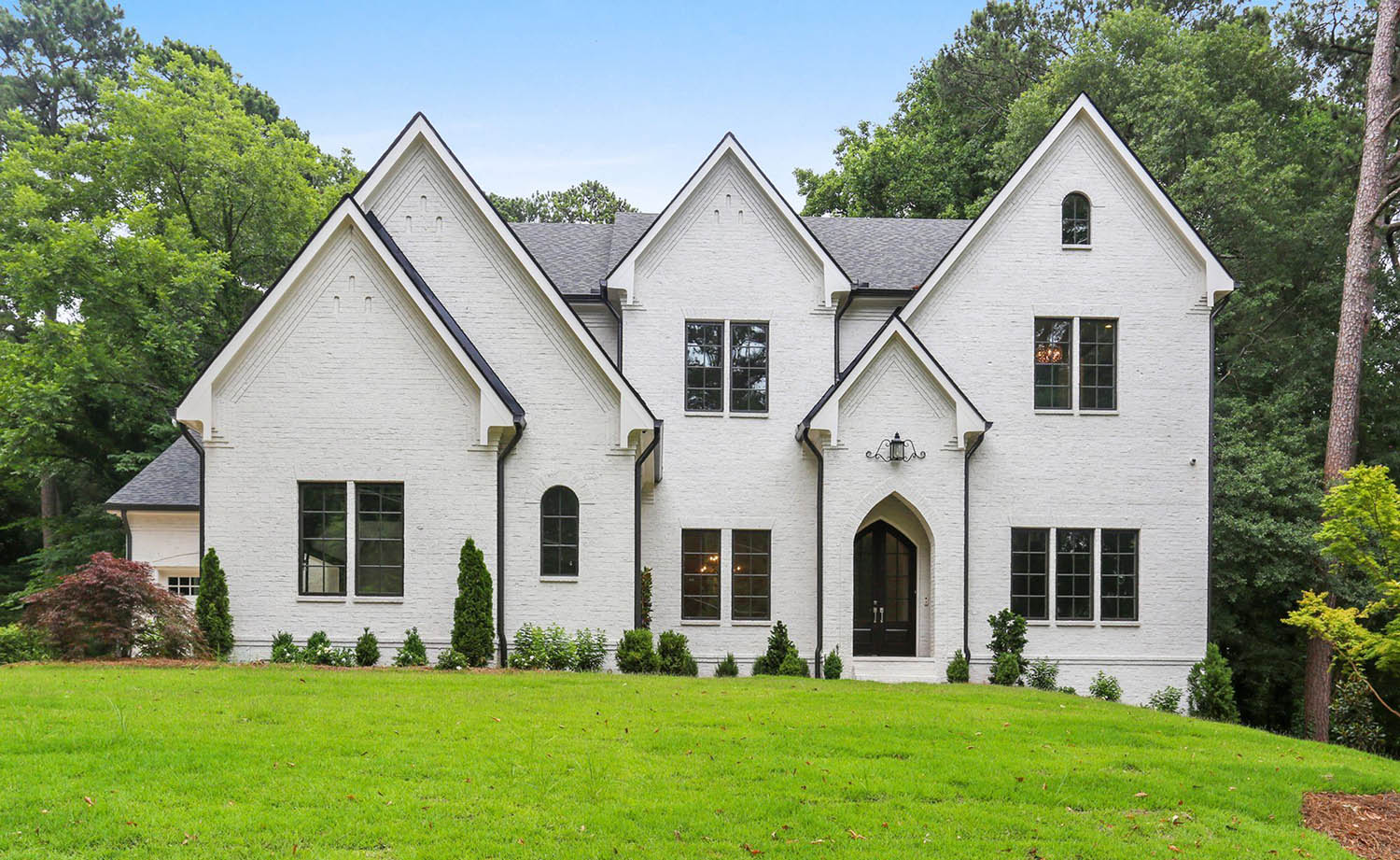painted white brick house with black framed windows and a black front door with black gutters